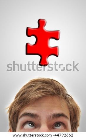 Man looking up at puzzle peice, problem solving his mind out. - stock photo