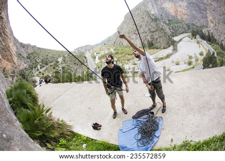 Man looking up at the mountain he is about to climb - stock photo