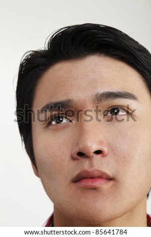 Man looking up with worried expression - stock photo
