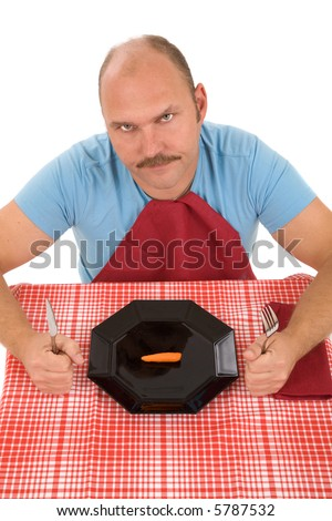Man looking very unhappy with the carrot on his plate - stock photo
