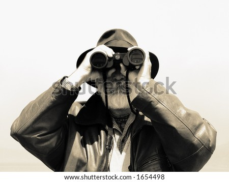Man looking with binoculars. Older explorer watching nature with binoculars