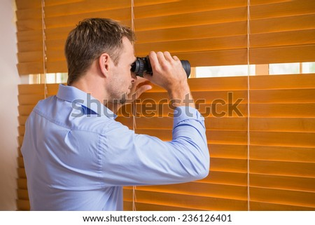 Man looking with binoculars through the blinds in the office - stock photo