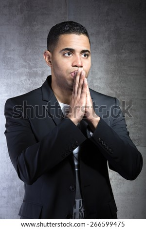 man looking with expectation and hands in his mouth on a gray background / young man with expression of hope facing forward - stock photo