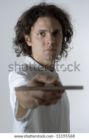 Man looks angry as he holds a table tennis paddle out in front of him. Vertically framed photograph - stock photo