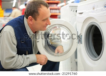 Man looks at washing machine in store