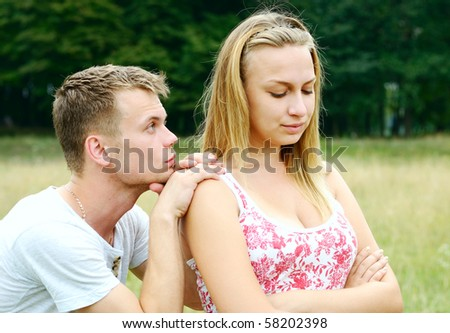 Man looks frustrated standing behind his girl - stock photo