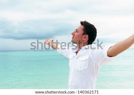 Man looks into the distance on the background of beautiful ocean with blue water and cloudy sky - stock photo