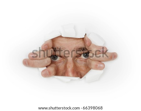 Man looks out from hole in white paper - stock photo