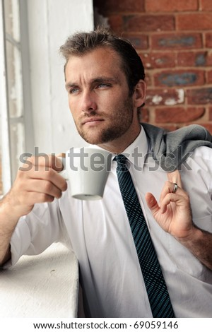 Man looks out the window thoughtfully, nice portrait of a businessman - stock photo