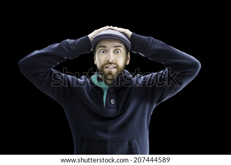 Man looks serious putting his hands on the head isolated on black - stock photo