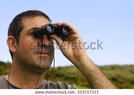 Man looks through binoculars outdoors. Concept photo of curious, spy, search, surveillance,spying,peeping, nosy man.