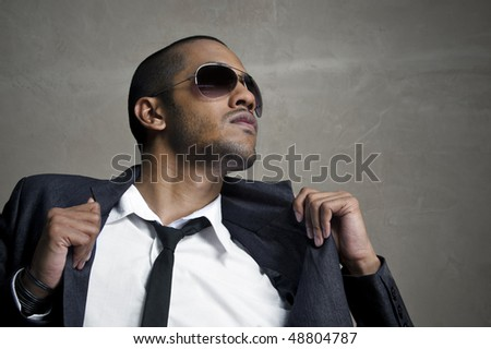 Man looks up as he holds his suit jacket - stock photo