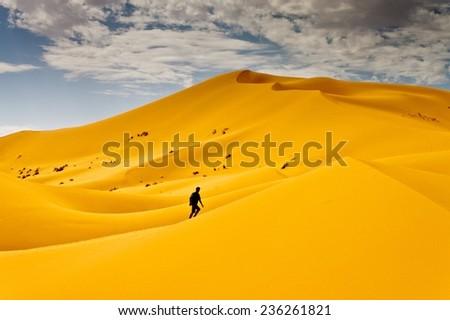 Man lost in desert dunes - stock photo