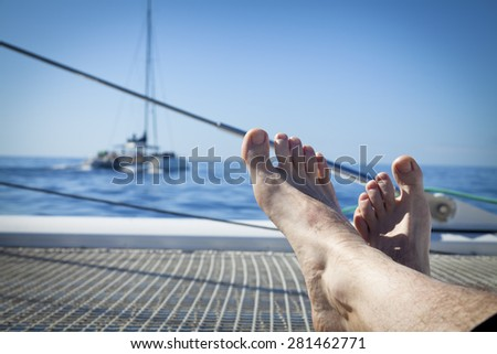 man lounging on a catamaran sailboat trampoline with her feet propped up and crossed. calm blue ocean and cloudless blue sky are in the background. copy space available - stock photo