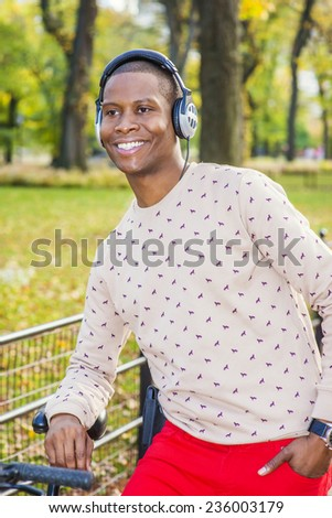 Man Love Music. Dressing in patterned collarless sweater, red pants, wearing headphones, a young black guy is tilting on a bike on the park, smiling, happily looking forward. Autumn Outing. - stock photo