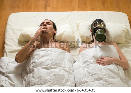 man lying in bed and smoking - stock photo