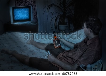 Man lying in bed and watching tv with bottle of whiskey