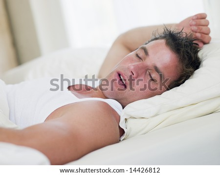 Man lying in bed sleeping - stock photo