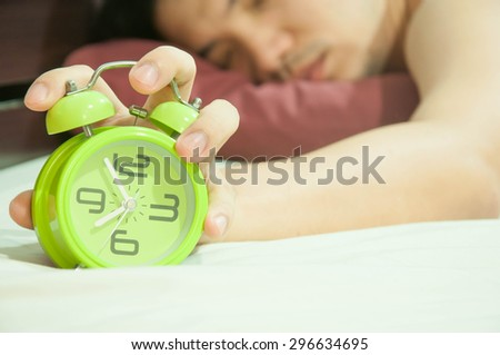 Man lying in bed turning off an alarm clock in the morning at 8am - stock photo