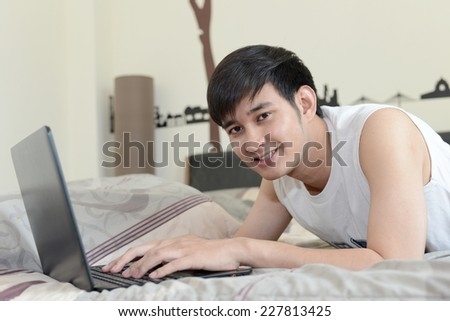 Man lying in bed with his laptop - stock photo