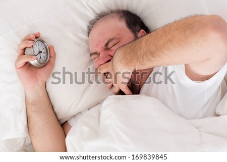 Man lying in bed yawning as he tries to wake up with his alarm clock clutched in his hand - stock photo