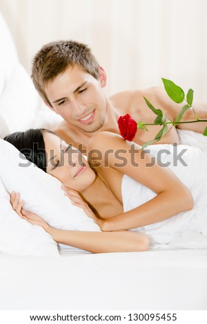Man lying in bedroom gives red rose to woman. Concept of love and affection