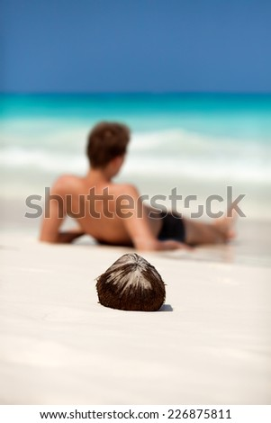 Man lying on a beach on a desert tropical island. Focus on coconut.