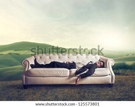 Man lying on a white sofa in a large field - stock photo