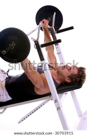 Man lying on bench and doing weightlifting - stock photo