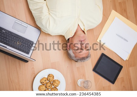 Man lying on floor surrounded by various objects at home in the living room - stock photo