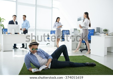 Man lying on green meadow in the center of the office and reading a book