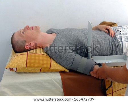 Man lying on hospital bed having blood pressure checked. - stock photo