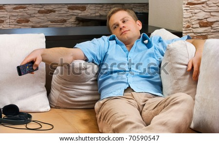 Man lying on sofa watching TV at home. - stock photo
