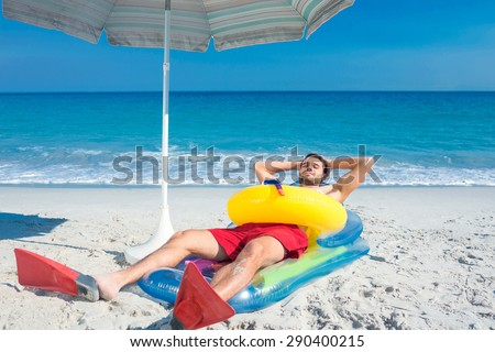Man lying on the beach with flippers and rubber ring on a sunny day - stock photo