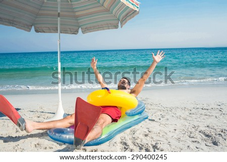 Man lying on the beach with flippers and rubber ring on a sunny day