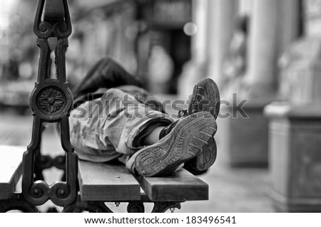 Man lying on the bench - stock photo