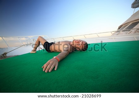 Man lying on the boat - stock photo