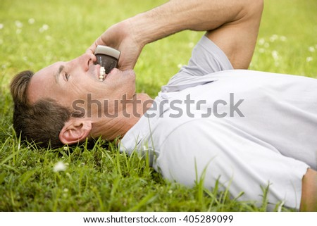 man lying on the grass talking on mobile phone - stock photo
