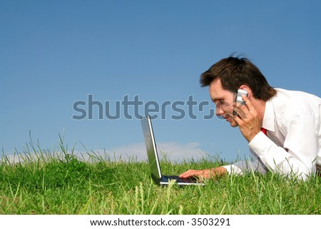Man lying on the grass using laptop - stock photo