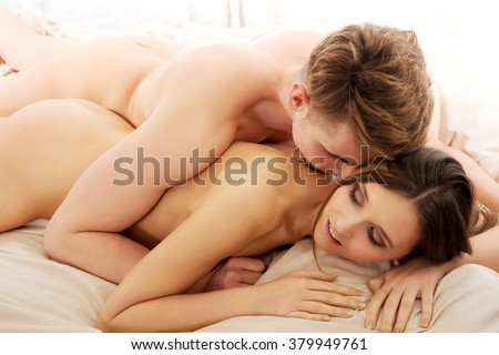 Man lying on woman in bedroom.