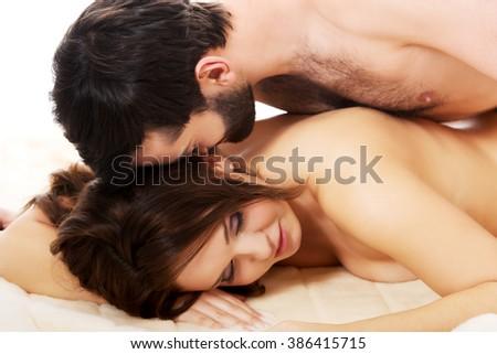Man lying on women in bedroom. - stock photo