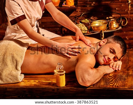 Man  lying on wooden boards having oil Ayurveda spa treatment. - stock photo