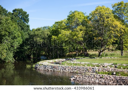 Man made fish ladder pathway and scenic riverbanks - stock photo