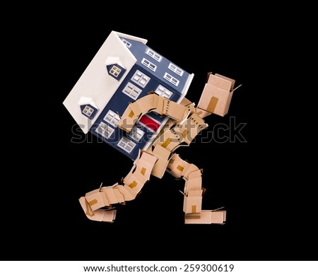 Man made of boxes carrying a house on his back with a black background - stock photo