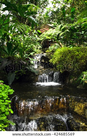 Man-made waterfall  surrounded by lush foliage in a landscaped garden - stock photo
