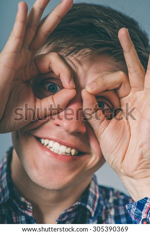 man makes binoculars hands