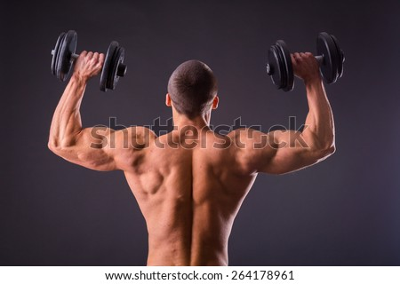 Man makes exercises dumbbells. Sport, power, dumbbells, tension, exercise. Article about fitness and sports.Gym and fitness concept - bodybuilder and dumbbell over black. - stock photo