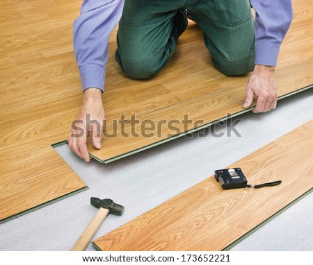 Man makes laying laminated panels color of wood - stock photo