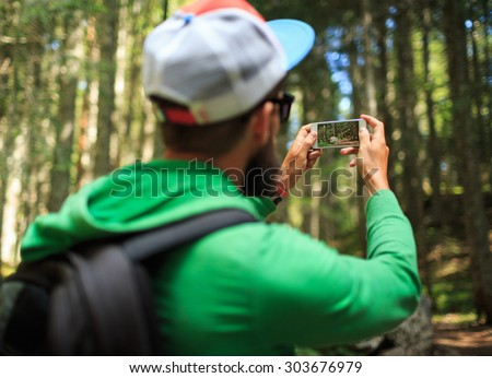 Man makes photos on a smartphone in the coniferous forest in the national park Durmitor, Montenegro, Balkans - stock photo