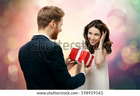 Man makes present to his lovely sweetheart on abstract and fantasy background - stock photo